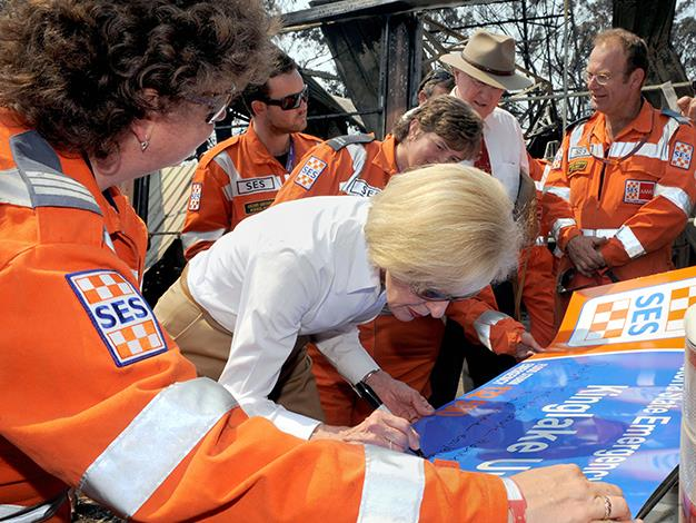 Quentin Bryce signs the state emergency service Kinglake unit sign during a meeting with volunteers near Kinglake on February 15, 2009. Bryce was there to pay tribute to the town that was virtually destroyed during the recent bushfire disaster which killed at least 181 people.