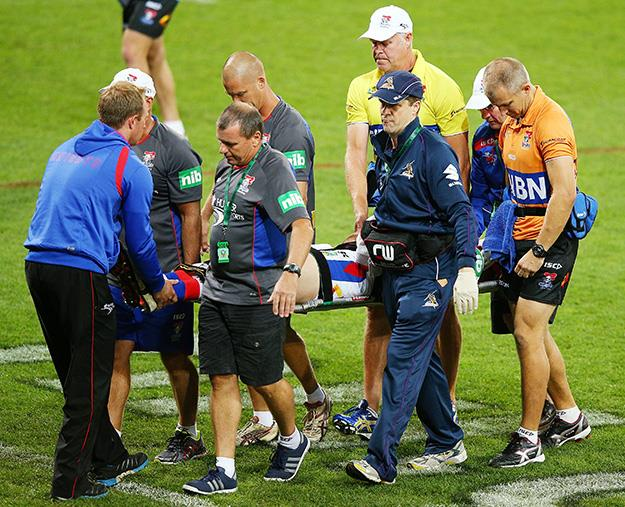 Alex McKinnon is carried off on a stretcher after being tackled.