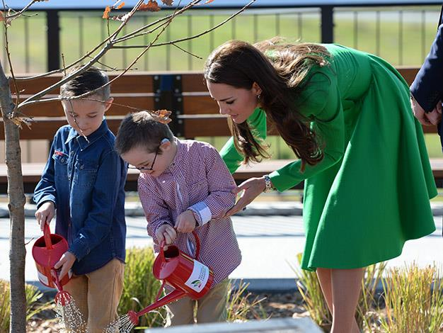 Two little volunteers water the oak tree with the Duchess' help. Photo: Splash Media