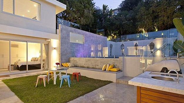The modern outdoor area comes complete with pool and barbecue.
