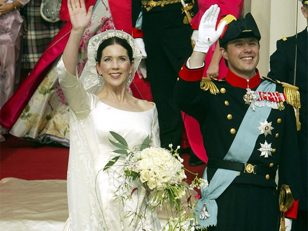The newlyweds wave to crowds following their wedding ceremony.