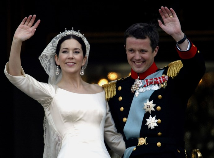 The happy couple wave to crowds on their wedding day.