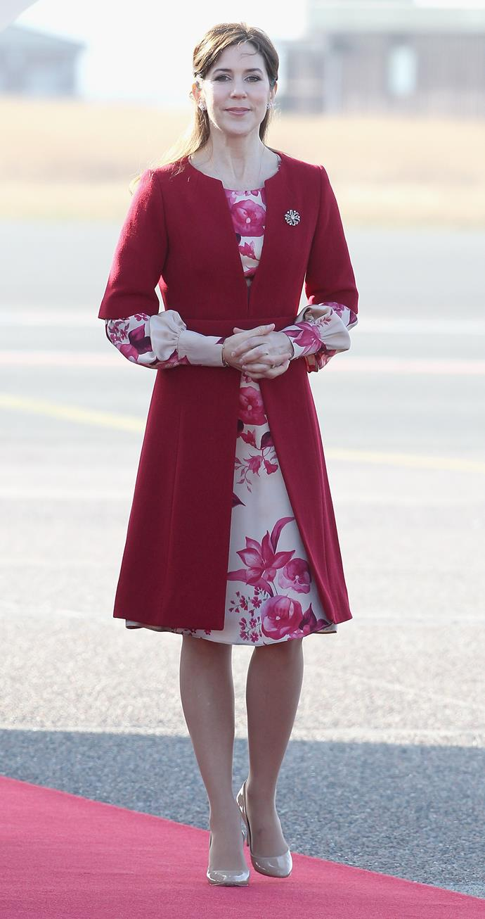 The royal sports a cherry red coat over a full sleeved floral dress and caps off the look with some patent nude pumps.