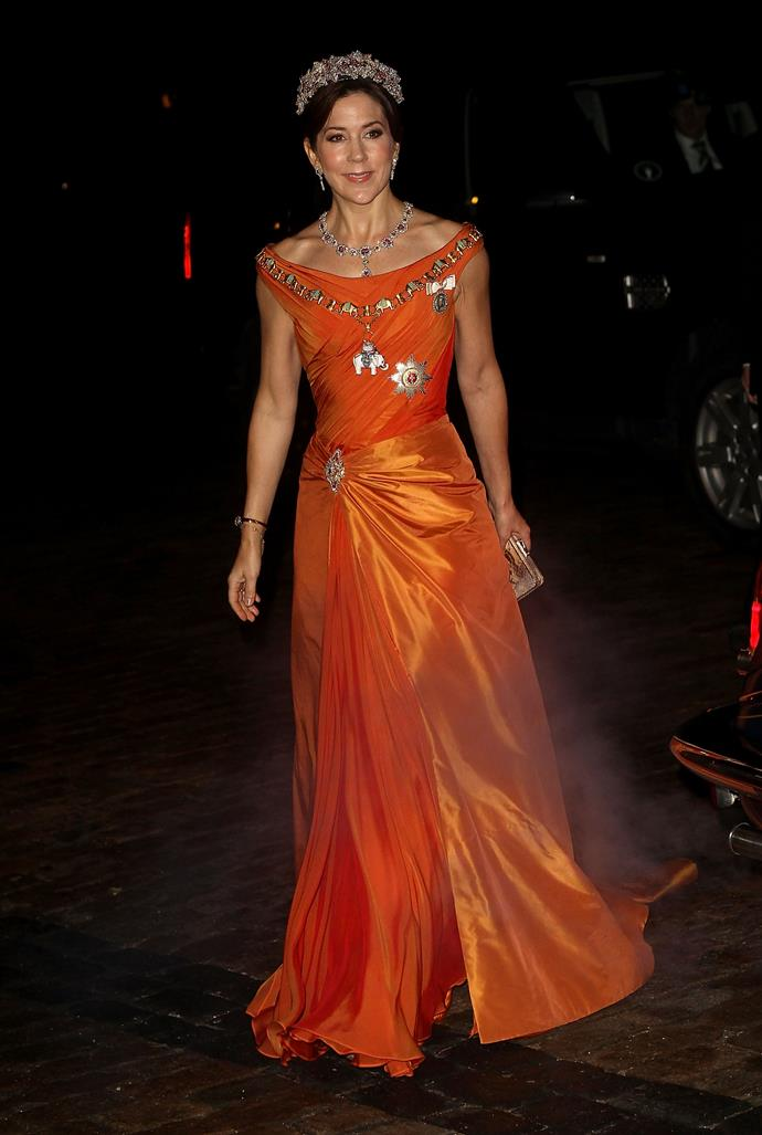 This festive tangerine gown that Mary wore to a New Year's Banquet hosted by Queen Margrethe will go down as one of her most celebrated looks yet.