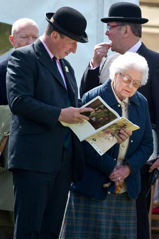 Her Majesty looked over the day's program with a friend. Photo: Getty