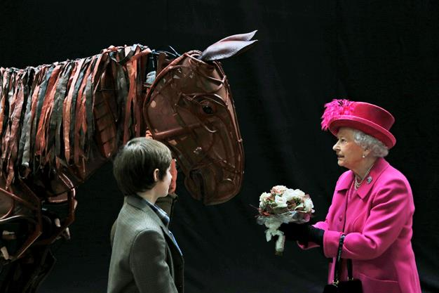 The Majesty receives flowers from a child actor as she inspects the horse prop from the theatre production 'War Horse' during a visit to the National Theatre in London in October 2013. Photo: Getty
