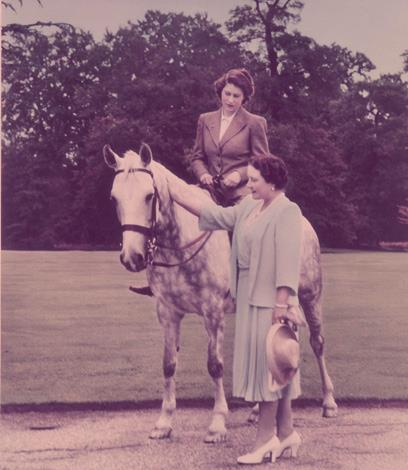 The Queen Mother standing next to Princess Elizabeth who is on a horse at the Royal Lodge in Windsor in England in 1946. Photo: Getty