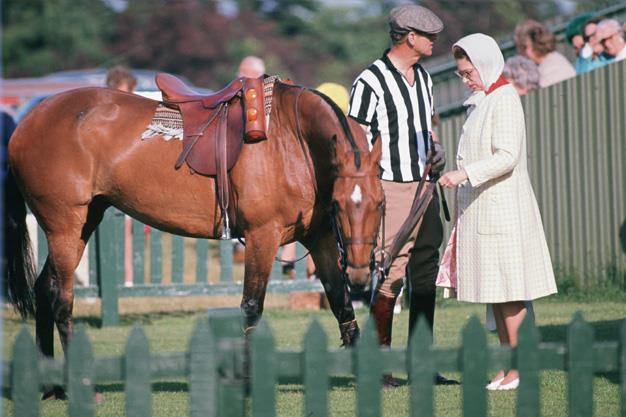 Queen Elizabeth II and Prince Philip, dressed as an umpire, at Smith's Lawn Polo Cub in 1973. Photo: Getty