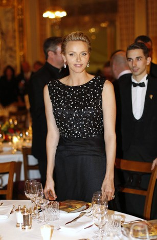 Charlene looking demure in a bejeweled high neck dress and earrings as attends the St David's Day gala dinner in March.