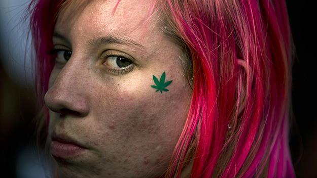 Woman with tattoo of marijuana leaf on her leaf