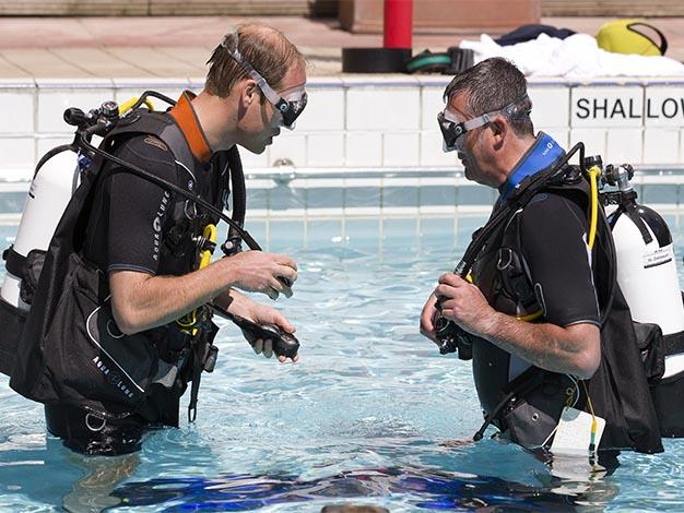 Prince William makes safety checks with BSAC Chairman Eugene Farrell before scuba diving.