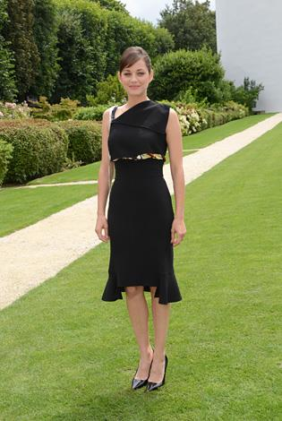 Marion Cotillard attends the Christian Dior fashion show in Paris in this one shouldered cocktail-style dress.