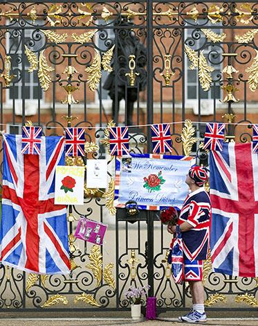 A man places flowers at the gates of Kensington Palace.