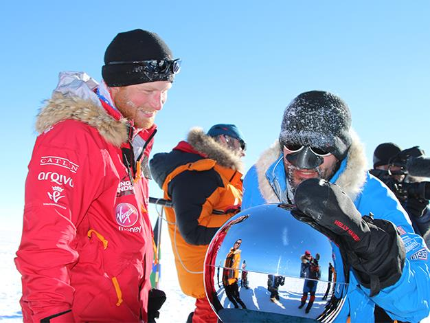 Prince Harry and Ivan Castro touch the pole as they and their fellow adventurers reach the South Pole for Walking with the Wounded.