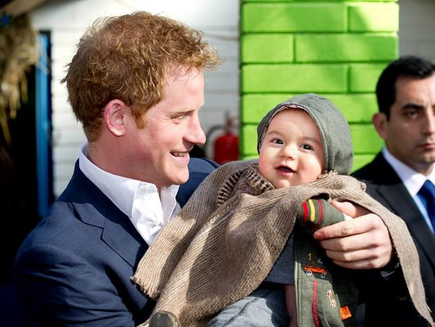 Harry holds young Matias Gonzalez as he visits the Sagrada Familia kindergarten during this year's visit to Chile.