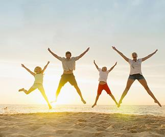 People jumping up in the air sunset beach, stock image