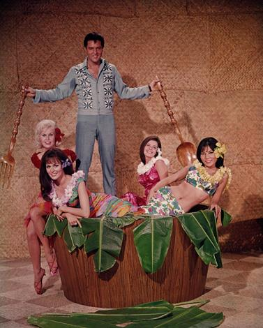 Here is Elvis in moviestar mode standing over a salad bowl full of girls in Hawaiian outfits and banana leaves with a fork and a spoon in a promo picture for the film *Paradise Hawaiian Style*. Fun Fact: The blonde actress is Suzanna Leigh who plays Judy Hudson.