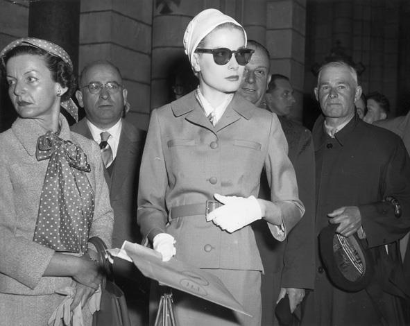 1956: American actress Grace Kelly wearing sunglasses and a cloche hat during her wedding rehearsal at Monaco Cathedral.