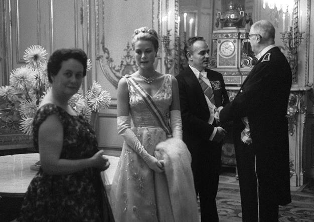 1959: French President Charles de Gaulle talks with Prince Rainier of Monaco as wifes Yvonne and Princess Grace stand close by.