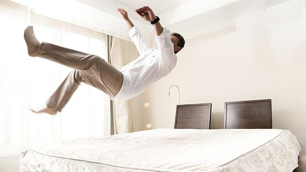 man jumping on bed, getty