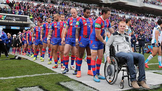 Knights players wheel Alex McKinnon onto the ground during a match between the Knights and Titans.
