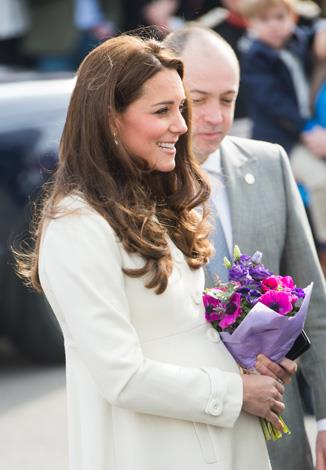 Kate wore a crisp white maternity coat by designer JoJo Maman Bébé and left her locks down for the visit.