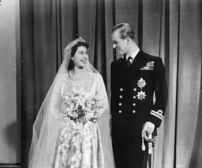 Using rations to buy the materiel for her dress, Queen Elizabeth, then Princess Elizabeth, wore a silk and lace gown with circular embroidery. She wore her grandmother's Fringe Tiara to match.