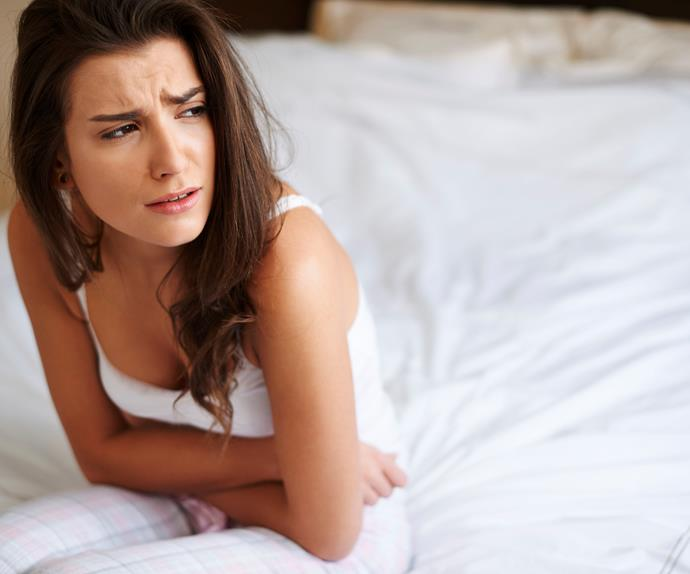 woman holding stomach on bed