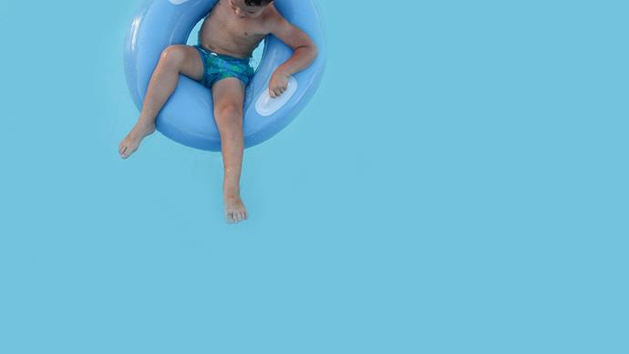 Boy sitting in flotation ring in pool.