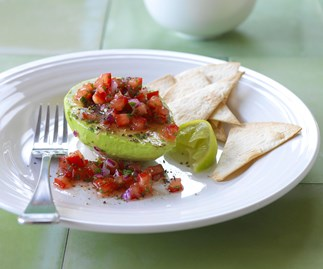 Half an avocado filled with tomato and onion salsa.