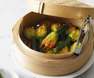 Zucchini flowers stuffed with ricotta and lemon in a steamer basket