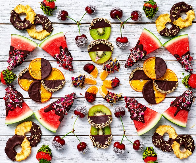 A variety of tropical fruits dipped in chocolate and toppings.