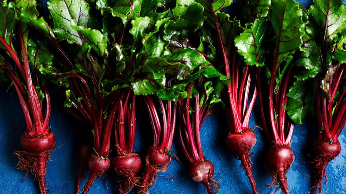 Fresh beetroot next to a jar of pickled beetroot.
