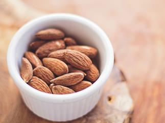 roasted and salted almonds in a white ramekin on a wooden table