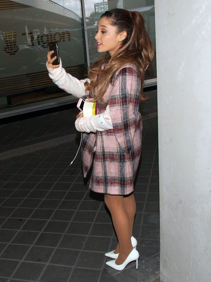 Even when she's catching a trans-Atlantic flight, Ariana never forgets her heels and her hair.
