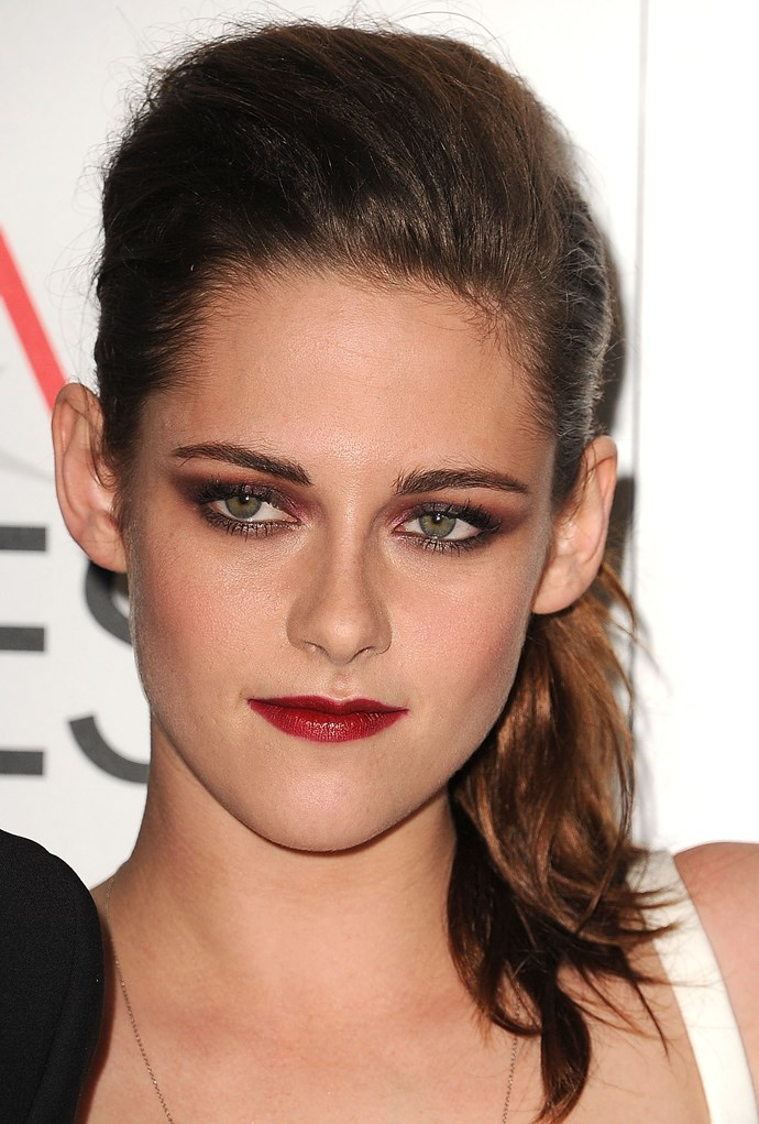 Kristen dons a slicked back pony to leave focus on her power brows and vampy red lips.