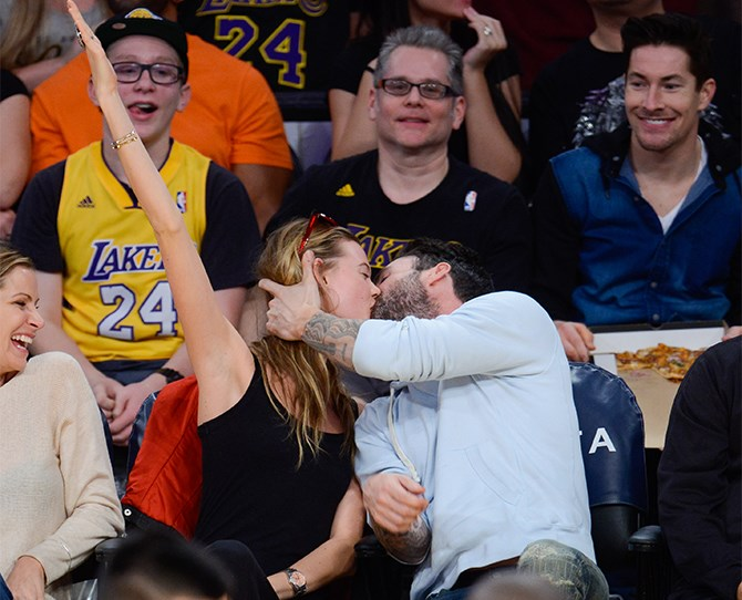 Beautiful couple Adam Levine and Behati Prinsloo got their PDA on at an LA Lakers game this week. Those three behind them have obviously just realised they've hit the seating jackpot.