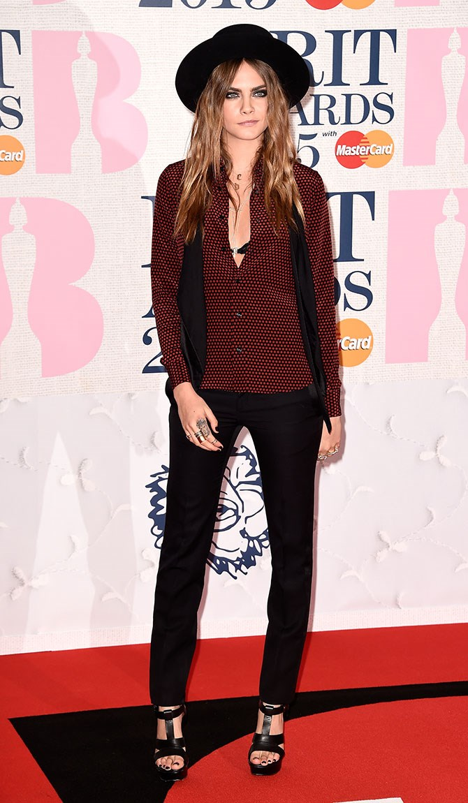 Cara Delevingne let her inner hipster reign by wearing a hat indoors on the Brit Awards red carpet. Of course, she owns it.