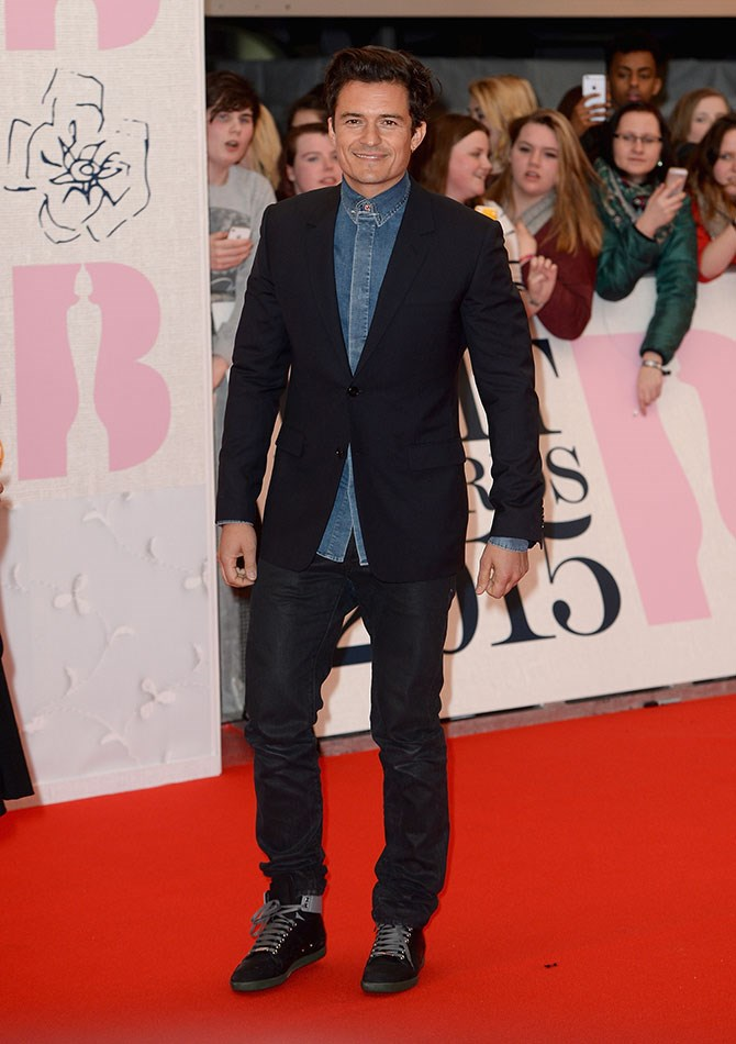 Orlando Bloom decided to safety pin the top of his denim shirt together. Hey, Orly, we'd sew your button back on ANY DAY.