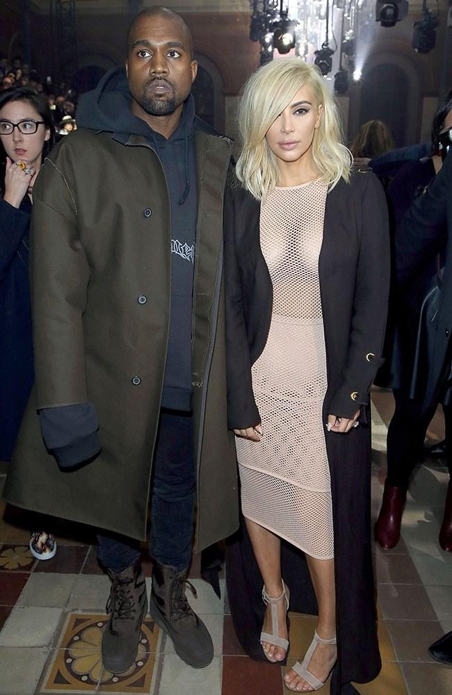 Kim tones downs her revealing mesh dress with a sleek trench. Kinda.
