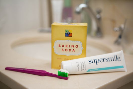 **12. Sprinkle baking soda on top of your whitening toothpaste to help remove surface stains.** Baking soda can be effective when it comes to polishing your pearly whites because it's a mild abrasive, meaning it won't hurt the enamel on your teeth (as long as it's rinsed away), but it will get into the harder-to-reach grooves, removing surface stains from coffee, wine, etc.