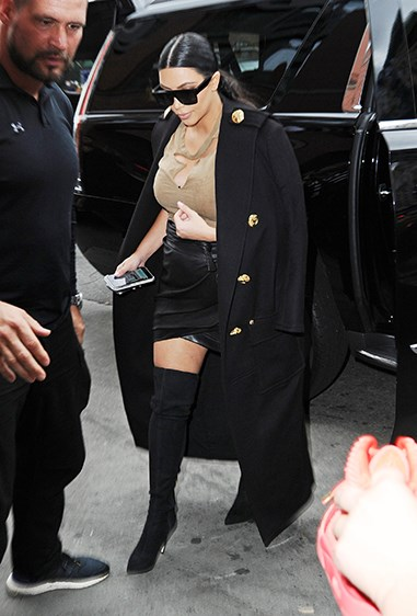 Kim looked FROW-central in this luxurious overcoat and leather skirt