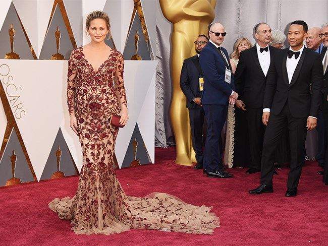 Chrissy Teigen takes her moment on the red carpet like the KWEEN that she is! She has gone proper red-carpet glam in this nude and burgundy, fishtail gown.