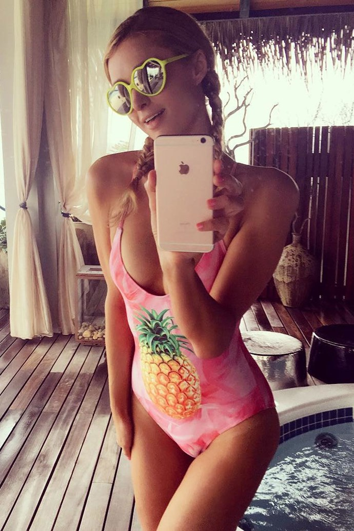 Only Paris Hilton could wear a bright pink pineapple swimsuit and neon yellow love-heart glasses in the year 2016 and make it look cool.