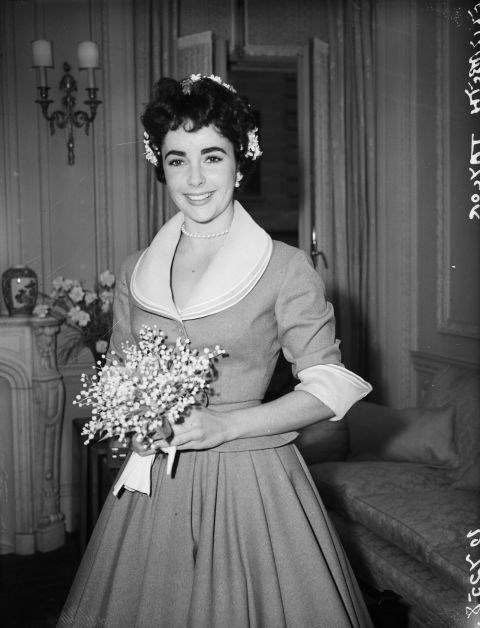 **1952: ELIZABETH TAYLOR**   While she wore several gowns for her many marriages, Elizabeth Taylor's first unconventional dress was this simple suit for her 1952 wedding to second husband Michael Wilding.
