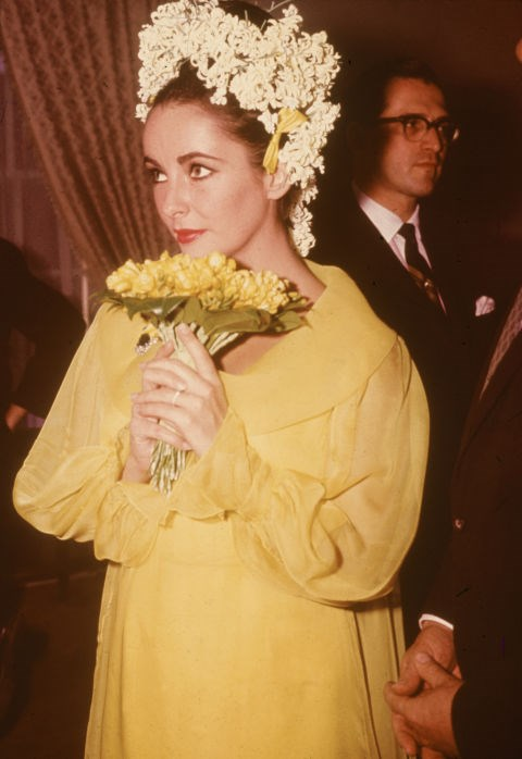 """**1964: ELIZABETH TAYLOR**   For her wedding to fifth husband Richard Burton, Taylor opted for a canary yellow chiffon dress topped off with dozens of white flowers in her hair. While her penchant for getting married certainly made the news more than her gowns, this dress *definitely* falls into the """"unconventional"""" category."""