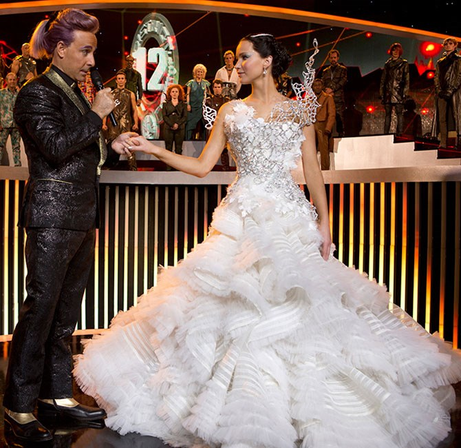 **Katniss Everdeen - *The Hunger Games: Catching Fire*** Katniss' trumpet-style dress is one helluva gown with metal applique, tulle frills and ruffles that went FOR DAYS. TBF, it was always meant to be a statement dress ('cause no one in The Capitol could sense her and Peeta's secret plan) but the fact it caught fire as she spun round and transformed into a slip for the reception was just the cherry on top.