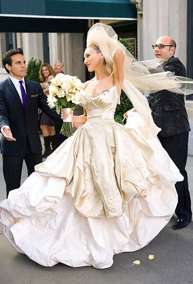 **Carrie Bradshaw - *Sex And The City*** Remember when Carrie was just 'gifted' this next-level Vivienne Westwood gown after she saw how amazing she looked wearing it? Yup, we still can't believe it either, but hell do we *want* to think that miracles like this happen IRL. Anyways, it was chic AF ('cause Viv), and in this pic you can just pretend that blue feather sitch never happened.