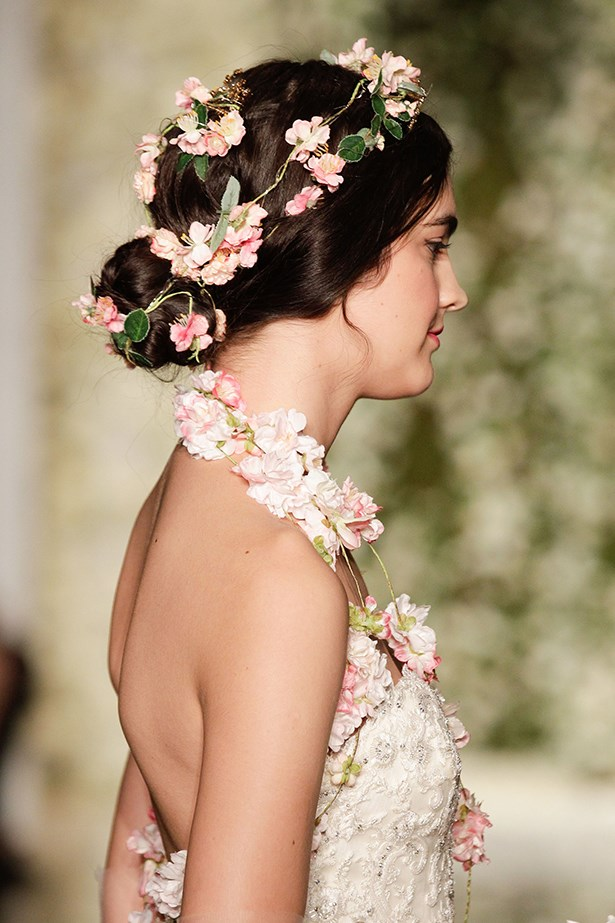 Calling all romantic types. Reem Acra showed the prettiest alternative to the ubiquitious flower crown at NYC's bridal fashion week. Loose, nape-sitting buns made the perfect base for petal-adorned locks. <br><br> Reem Acra bridal fashion week autumn winter 2015