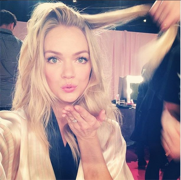 Lindsay Ellingson blows a kiss while getting her hair styled backstage.